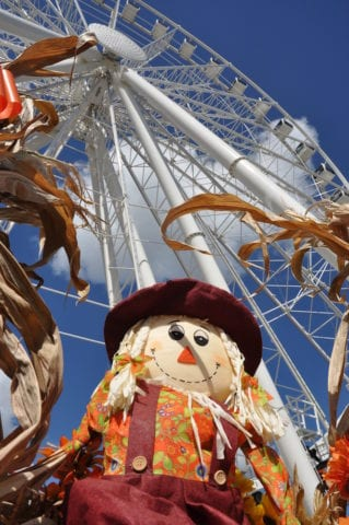 A scarecrow smiling in front of the wheel at the Island in Pigeon Forge