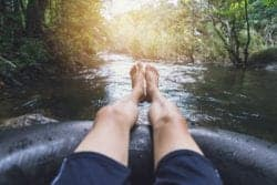 man's legs on inner tube in river