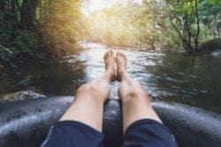man's legs on inner tube in river