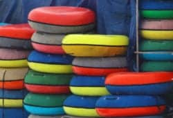 colorful inner tubes stacked next to a wall